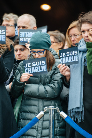 shootings: STRASBOURG, FRANCE - JANUARY 09, 2015: Council of Europe employees holding JE SUIS CHARLIE poster during a silent vigil to condemn the gun attack at French satirical magazine Charlie Hebdo office in Paris, which killed 12 people on January 7, 2015