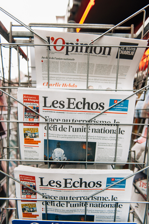 shootings: STRASBOURG, FRANCE - 10 JAN, 2015: The front covers of International newspapers display headlining the terrorist attacks yesterday in Paris on January 8, 2015 Editorial