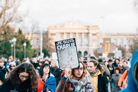 STRASBOURG, FRANCE - 11 JAN, 2015:  Girl hold placards reading Je suis Charlie during a unity rally (Marche Republicaine) where some 50000 people took part in tribute three-day killing spree in Paris Editorial