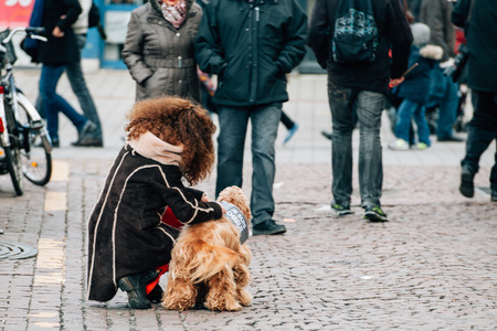 attaching: STRASBOURG, FRANCE - 11 JAN, 2015:  Girl attaching to her dog plancard Je suis Charlie during a unity rally (Marche Republicaine) where some 50000 people took part in tribute three-day killing spree in Paris Editorial