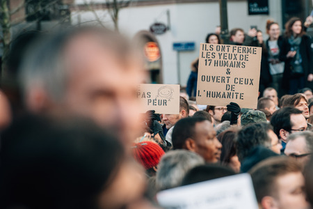 shootings: STRASBOURG, FRANCE - 11 JAN, 2015:  People hold placards reading They close the eyes of 17 people but opened the humanity ones during a unity rally (Marche Republicaine) where some 50000 people took part in tribute three-day killing spree in Paris