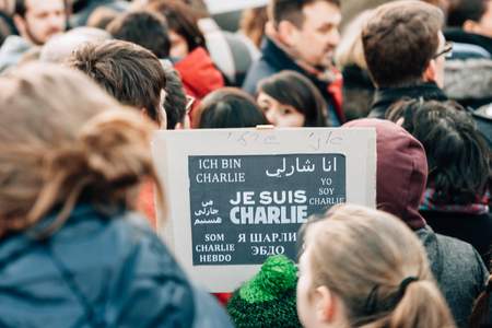 shootings: STRASBOURG, FRANCE - 11 JAN, 2015:  People hold placards reading Je suis Charlie in foreign languages during a unity rally (Marche Republicaine) where some 50000 people took part in tribute three-day killing spree in Paris