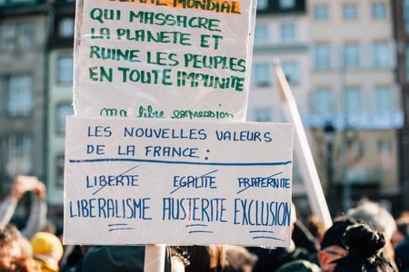 exclusion: STRASBOURG, FRANCE - 11 JAN, 2015:  People hold placard reading Liberalism, Austerity, Exclusion during a unity rally (Marche Republicaine) where some 50000 people took part in tribute three-day killing spree in Paris