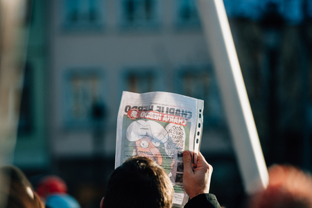 satirical: STRASBOURG, FRANCE - 11 JAN, 2015:  People holding Charlie Hebdo cover with Mohammed cartoon during a unity rally (Marche Republicaine) where some 50000 people took part in tribute three-day killing spree in Paris
