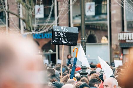 part of me: ESTRASBURGO, Francia - el 11 de enero 2015: La gente sostiene pancartas que dec�an 'me r�o, luego existo' durante una manifestaci�n unitaria (Marche Republicaine) donde algunos 50.000 personas participaron en el tributo de tres d�as Asesinato m�ltiple en Par�s Editorial