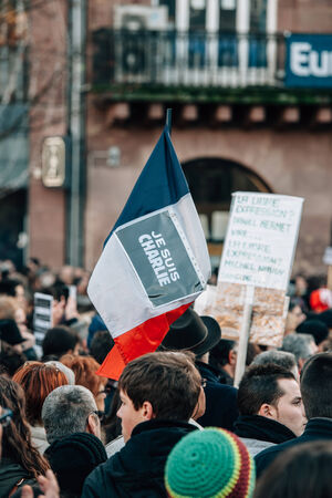 satirical: STRASBOURG, FRANCE - 11 JAN, 2015:  People hold placards reading Je suis Charlie on a French flag during a unity rally (Marche Republicaine) where some 50000 people took part in tribute three-day killing spree in Paris