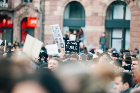 shootings: STRASBOURG, FRANCE - 11 JAN, 2015:  People hold placards reading Je suis Charlie during a unity rally (Marche Republicaine) where some 50000 people took part in tribute three-day killing spree in Paris