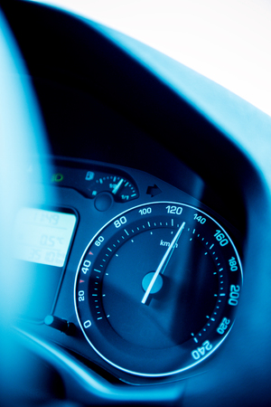 FRANKFURT AM MAIN, GERMANY - DECEMBER 22, 2013: Speedometer close-up with the needle pointing a high 140 kmmph speed, blur effect and blue tone to depict high speed concet and security driving photo