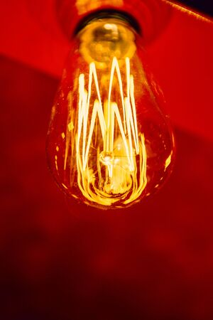 efficiently: Red light bulb close-up glowing on a red elegant background