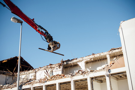 old office: A long-reach excavator pulling apart an old office block.  Stock Photo