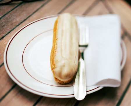 Eclaire - french oblong pastry chocolate desert made with choux dough filled with a cream and topped with icing on a wooden cafe table photo