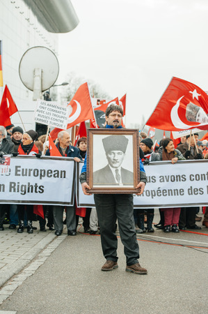 the case before: STRASBOURG, FRANCE - 28 JAN 2015 Man holding Ataturk portrait during demonstration near European Court of HR before the Perincek vs. Switzerland case begin. Armenian government was represented by Amal Clooney Editorial