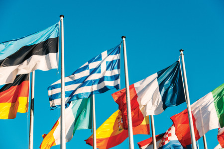 austerity: Greece flag waving in front of European Parliament, next to Estonia, France, Italian, Spain, Germany flags on a clear blue sky