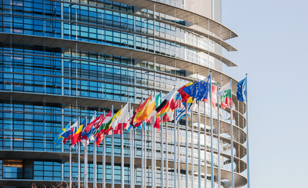 STRASBOURG, FRANCE - JANUARY 28, 2014: European Parliament facade with all EU European Union Country flags waving on a clear sky day. Horizontal shot Editoriali