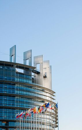 european parliament: STRASBOURG, FRANCE - JANUARY 28, 2014: European Parliament facade with all EU European Union Country flags waving on a clear sky day. Vertical shot