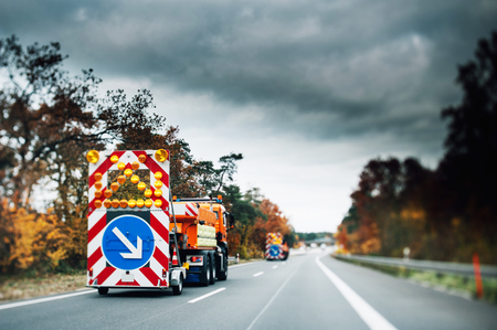 highway signs: Highway emergency securty trucks in a row with flashing large warning sign on a highway announcing danger and big storm ahead. Tilt-shift lens used for better contrast Stock Photo