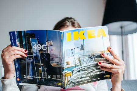 PARIJS, FRANKRIJK - 24 augustus 2014: Vrouw leest IKEA catalogus voor het kopen van meubels voor haar nieuwe huis. De catalogus wordt jaarlijks gepubliceerd door de Zweedse woninginrichting retailer en werd voor het eerst gepubliceerd in Zweedse in 1951. Wereldwijd zijn ongeveer 208 m Redactioneel