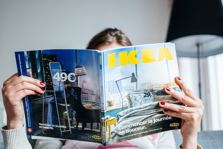 PARIS, FRANCE - AUGUST 24, 2014: Woman reading IKEA Catalogue before buying furniture for her new house. The catalogue is published annually by the Swedish home furnishing retailer and was first published in Swedish in 1951. Worldwide, approximately 208 m Banco de Imagens - 37430310
