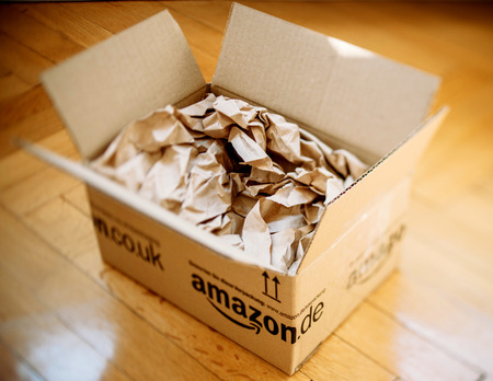 LONDON, UNITED KINGDOM - MARCH 05, 2014: Amazon.co.uk shipping package parcel box opened on wooden floor with protection paper inside. Amazon.com went online in 1995 and is now the largest online retailer in the world. 報道画像