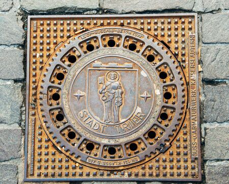 male likeness: TRIER, GERMANY - 22 FEV 2015: Detail shot of Trier - Treves manhole cover on cobblestone pavement featuring the iconic city logo - MOnk with Bible and Kay. Trier or Treves is the oldest city in Germany. It is also the oldest seat of a bishop north of the  Editorial