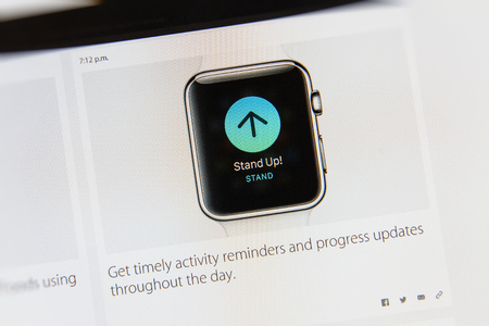 PARIS, FRANCE - MAR 9, 2015: Apple Computers event keynote tweets close up seen on iMac display with Stand Up command for progress updates throughout the day on Apple Watch display as seen on 9 March, 2015