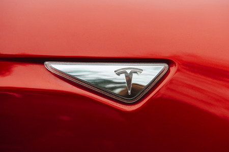chrom: PARIS, FRANCE - NOVEMBER 29: Tesla brand signage of a red environmentally friendly car. Tesla is an American company that designs, manufactures, and sells electric cars