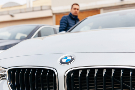 car dealership: MUNCHEN, GERMANY - APRIL 06, 2015: Man looking at electric BMW limousine outside car dealership. Editorial