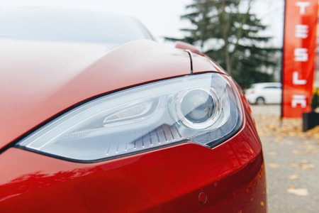 chrom: PARIS, FRANCE - NOVEMBER 29: Tesla Model S head light of a red electric car in Paris, France. Tesla is an American company that designs, manufactures, and sells electric cars Editorial
