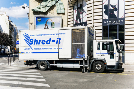 PARIS, FRANCE - AUGUST 18, 2015: Shred-it truck shredder outside a clients door on Paris street. Shred-it specializes in mobile on-site and off-site secure paper shredding and confidential waste disposal.