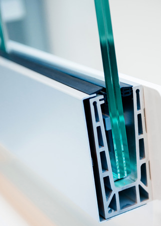 Cross section of a PVC window profile, beside a pvc window frame, over a plastic surface - thermal insulation and environment protection concept