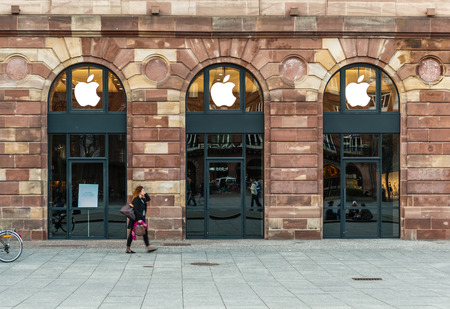 Woman walking in front of Apple Store which has covered shopping windows with black fabric curtains to protect the store rearrangement for the Apple Watch launch. Apples Watch with goes on sale in US, Europe and Asia on April 10