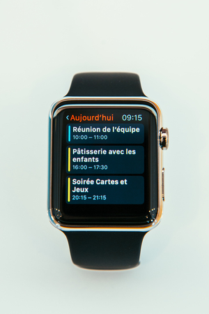 capabilities: PARIS, FRANCE – APR 10, 2014: New wearable computer Apple Watch smartwatch displaying the new Calendar app. It incorporates fitness tracking and health-oriented capabilities and  integration with iOS Apple products and services