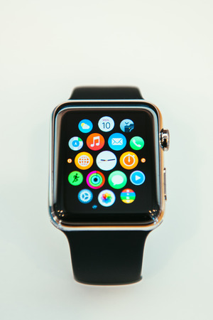 PARIS, FRANCE – APR 10, 2014: New wearable computer Apple Watch smartwatch displaying the new interface home screen. It incorporates fitness tracking and health-oriented capabilities and  integration with iOS Apple products and services