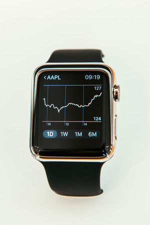 incorporates: PARIS, FRANCE – APR 10, 2015: New wearable computer Apple Watch smartwatch displaying the new Stocks App with Apple Stock Price Graph. Apple Watch incorporates fitness tracking and health-oriented capabilities and  integration with iOS Apple products an