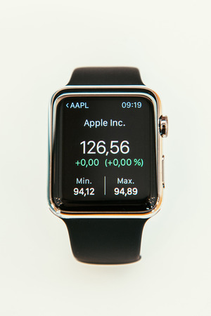 PARIS, FRANCE – APR 10, 2015: New wearable computer Apple Watch smartwatch displaying the new Stocks App with Apple Stock Price. Apple Watch incorporates fitness tracking and health-oriented capabilities and  integration with iOS Apple products and serv