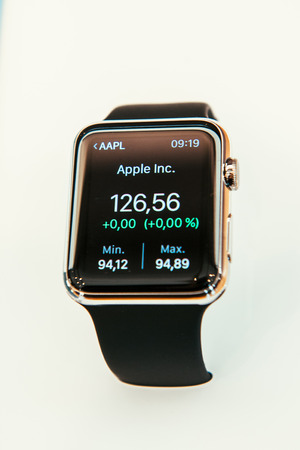 serv: PARIS, FRANCE – APR 10, 2015: New wearable computer Apple Watch smartwatch displaying the new Stocks App with Apple Stock Price. Apple Watch incorporates fitness tracking and health-oriented capabilities and  integration with iOS Apple products and serv