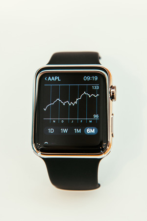 stock market graph: PARIS, FRANCE – APR 10, 2015: New wearable computer Apple Watch smartwatch displaying the new Stocks App with Apple Stock Price Graph. Apple Watch incorporates fitness tracking and health-oriented capabilities and  integration with iOS Apple products an Editorial
