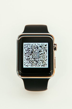 capabilities: PARIS, FRANCE – APR 10, 2015: New wearable computer Apple Watch smartwatch displaying the new Passbook App with QR code. Apple Watch incorporates fitness tracking and health-oriented capabilities and  integration with iOS Apple products and services