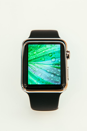 incorporates: PARIS, FRANCE – APR 10, 2015: New wearable computer Apple Watch smartwatch displaying the new Photo App. Apple Watch incorporates fitness tracking and health-oriented capabilities and  integration with iOS Apple products and services