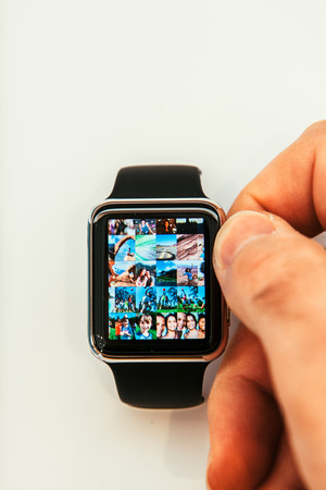 PARIS, FRANCE – APR 10, 2015: New wearable computer Apple Watch smartwatch displaying the new Photo App. Apple Watch incorporates fitness tracking and health-oriented capabilities and  integration with iOS Apple products and services Editorial