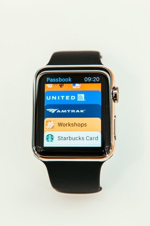 PARIS, FRANCE – APR 10, 2015: New wearable computer Apple Watch smartwatch displaying the new Passbook App. Apple Watch incorporates fitness tracking and health-oriented capabilities and  integration with iOS Apple products and services
