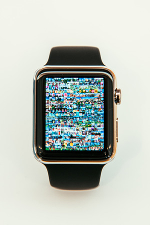 incorporates: PARIS, FRANCE – APR 10, 2015: New wearable computer Apple Watch smartwatch displaying the new Photo App . Apple Watch incorporates fitness tracking and health-oriented capabilities and  integration with iOS Apple products and services