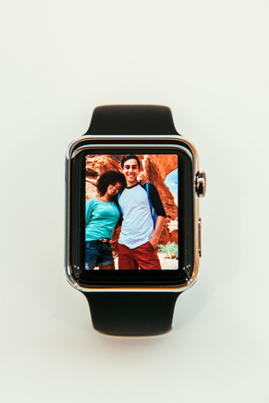 PARIS, FRANCE – APR 10, 2015: New wearable computer Apple Watch smartwatch displaying the new Photo App. Apple Watch incorporates fitness tracking and health-oriented capabilities and  integration with iOS Apple products and services
