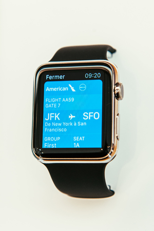 luxury watch: PARIS, FRANCE – APR 10, 2015: New wearable computer Apple Watch smartwatch displaying the new Passbook App showcasing an American Airlines Chek-In data. Apple Watch incorporates fitness tracking and health-oriented capabilities and  integration with iOS
