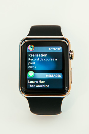 PARIS, FRANCE – APR 10, 2015: New wearable computer Apple Watch smartwatch displaying the new Action Center App. Apple Watch incorporates fitness tracking and health-oriented capabilities and  integration with iOS Apple products and services