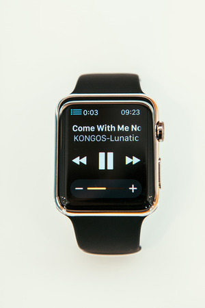 PARIS, FRANCE – APR 10, 2015: New wearable computer Apple Watch smartwatch displaying the new Remmote App and iTunes Library control. Apple Watch incorporates fitness tracking and health-oriented capabilities and  integration with iOS Apple products and Editorial