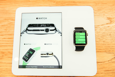 PARIS, FRANCE – APR 10, 2015: New wearable computer Apple Watch smartwatch displaying the new Sport Edition. Apple Watch incorporates fitness tracking and health-oriented capabilities and  integration with iOS Apple products and services