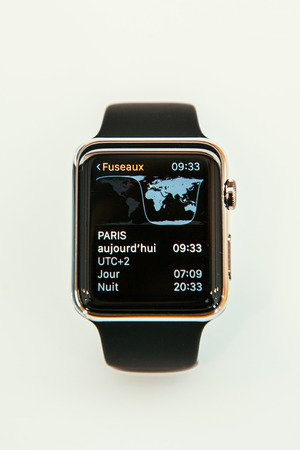 PARIS, FRANCE – APR 10, 2015: New wearable computer Apple Watch smartwatch displaying the new Time Zone App. Apple Watch incorporates fitness tracking and health-oriented capabilities and  integration with iOS Apple products and services