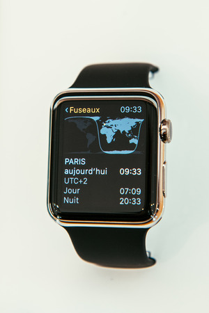 capabilities: PARIS, FRANCE – APR 10, 2015: New wearable computer Apple Watch smartwatch displaying the new Time Zone App. Apple Watch incorporates fitness tracking and health-oriented capabilities and  integration with iOS Apple products and services