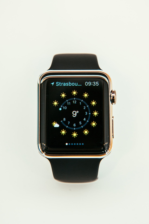 incorporates: PARIS, FRANCE – APR 10, 2015: New wearable computer Apple Watch smartwatch displaying the new Weather App. Apple Watch incorporates fitness tracking and health-oriented capabilities and  integration with iOS Apple products and services